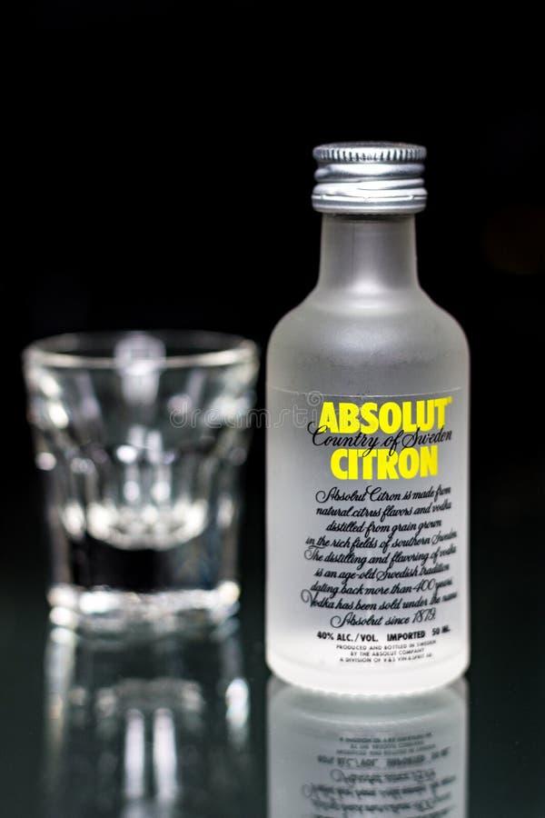 Una mini botella de vodka cítrica de Absolut con un vidrio foto de archivo