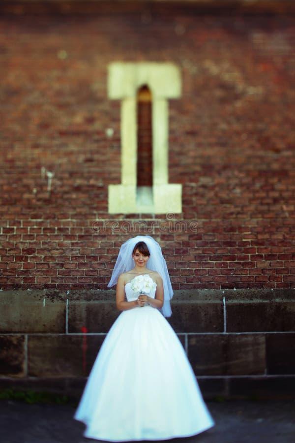 Una mirada lejos en de una novia que se coloca debajo de una pequeña ventana imagenes de archivo
