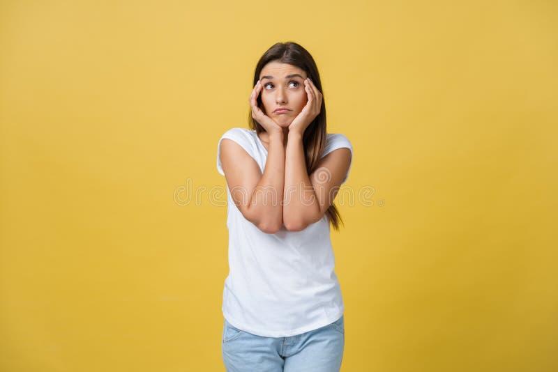 Una mirada que aboga por triste de una mujer atractiva joven aislada en las manos amarillas del retrato del estudio del fondo lig imagen de archivo