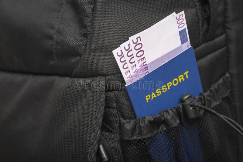 Una mochila cuyo de bolsillo un pasaporte y un dinero se están pegando hacia fuera en euros imagenes de archivo