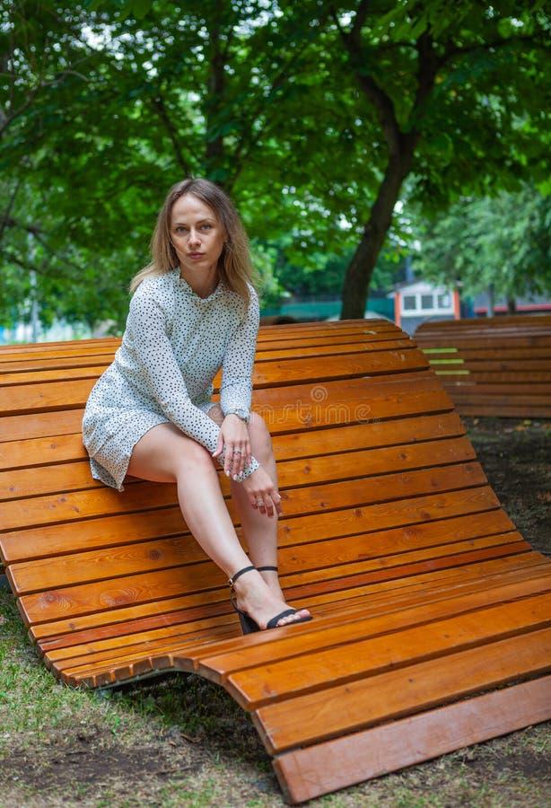Una modelo joven posando en un banco de madera imágenes de archivo libres de regalías