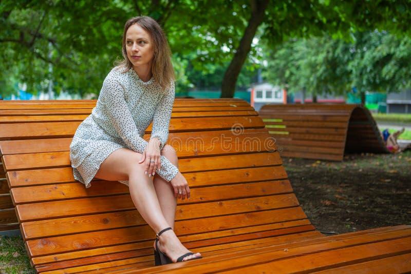Una modelo joven posando en un banco de madera fotos de archivo