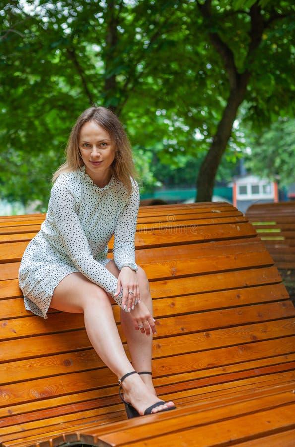 Una modelo joven posando en un banco de madera foto de archivo