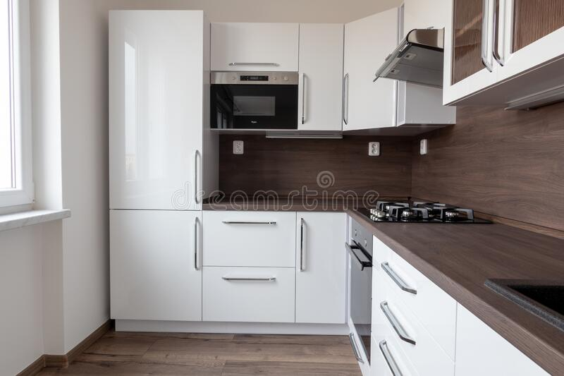 Una moderna cocina de madera en forma de L con un escritorio marrón oscuro, colores blancos y nevera incrustada fotografía de archivo