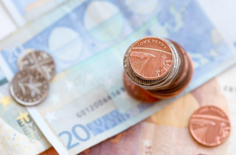 Una moneda británica del penique y billetes del euro imagenes de archivo