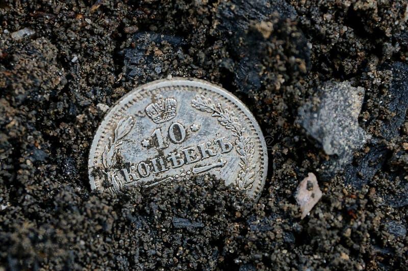 Una moneda de plata vieja blanca miente en tierra negra imágenes de archivo libres de regalías