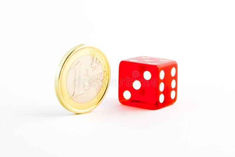 Una moneda euro y un dado rojo fotografía de archivo libre de regalías