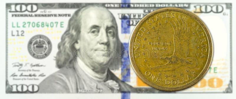 Una moneta del dollaro contro il complemento della banconota di 100 dollari fotografie stock