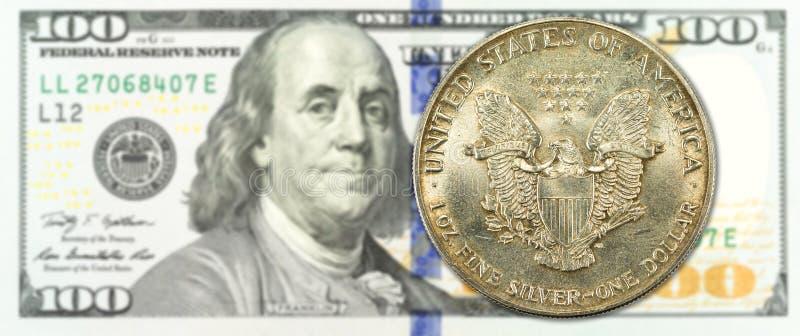 Una moneta del dollaro d'argento contro il complemento della banconota di 100 dollari immagine stock