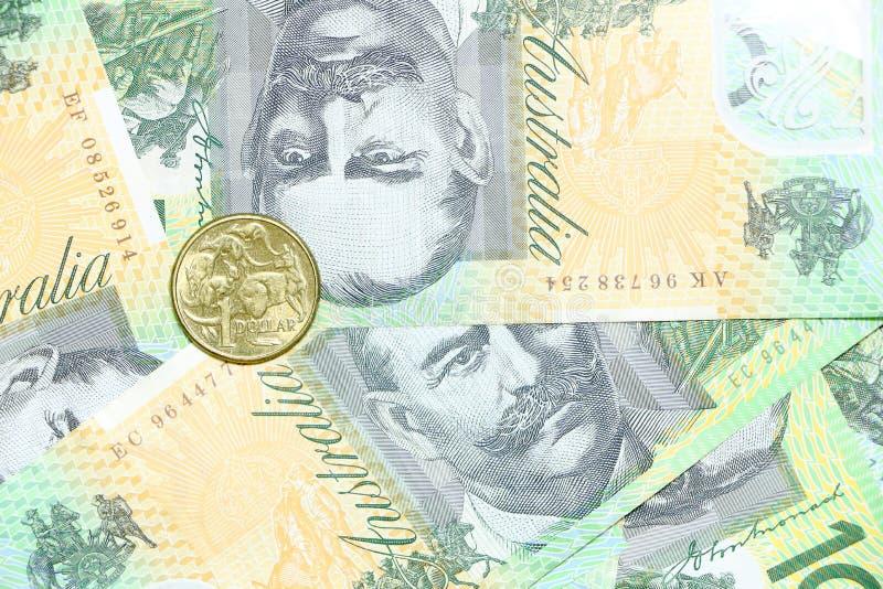 Una moneta del dollaro dell'AUD su un gruppo di fondo australiano del mucchio di 100 note del dollaro immagini stock