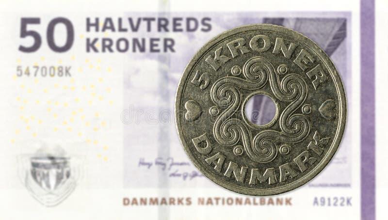 una moneta di 5 corone danesi contro una nota di 50 corone danesi fotografia stock libera da diritti