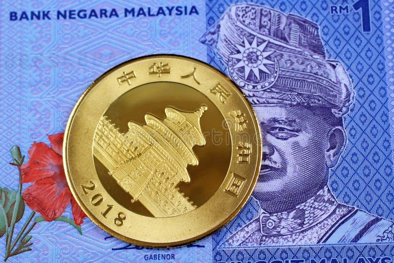 Una moneta di oro cinese con un'una banconota malese di ringgit fotografie stock