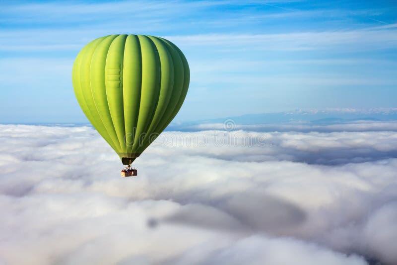 Una mongolfiera verde sola galleggia sopra le nuvole fotografie stock