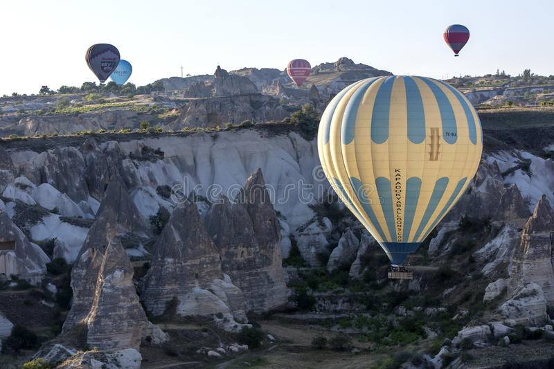 Una mongolfiera vola giù la valle di amore all'alba vicino a Goreme nella regione di Cappadocia di Turchia immagine stock libera da diritti