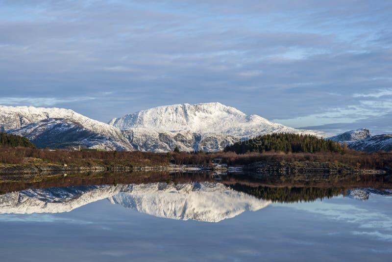 Una montagna fredda bianca riflette nel mare su un fondo blu-grigio fotografia stock libera da diritti