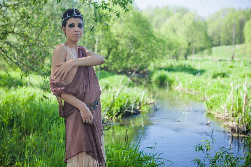 Una morenita fina en un vestido marrón con una corona en su cabeza miente en una rama de árbol cerca de una charca del bosque fotos de archivo