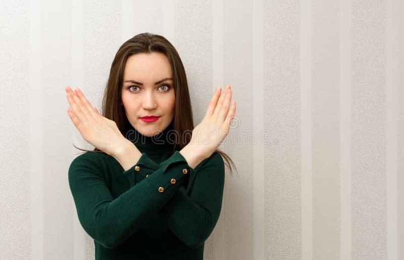Una morenita hermosa de pelo largo muestra los brazos cruzados delante de ella Concepto de prohibición imagen de archivo