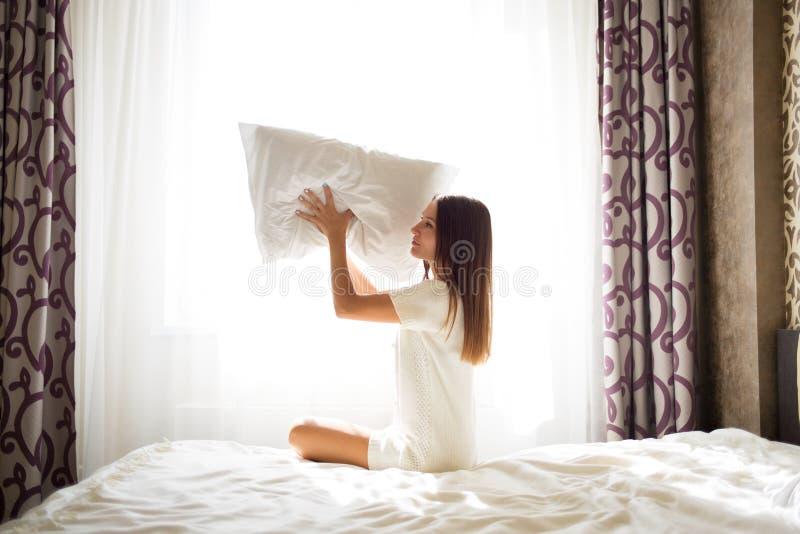 Una morenita hermosa se sienta en una cama y lanza una almohada foto de archivo