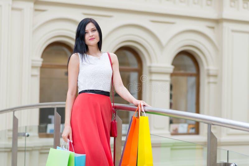 Una morenita joven hermosa con muchos bolsos de las tiendas de lujo Compras, venta, regalos y conceptos de los días de fiesta imagen de archivo libre de regalías