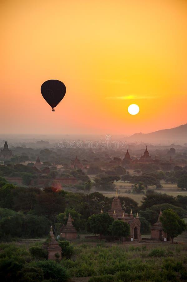 una mosca del globo del aire caliente sobre la ciudad antigua Bagan myanmar cuando mañana de la subida del sol imagen de archivo libre de regalías