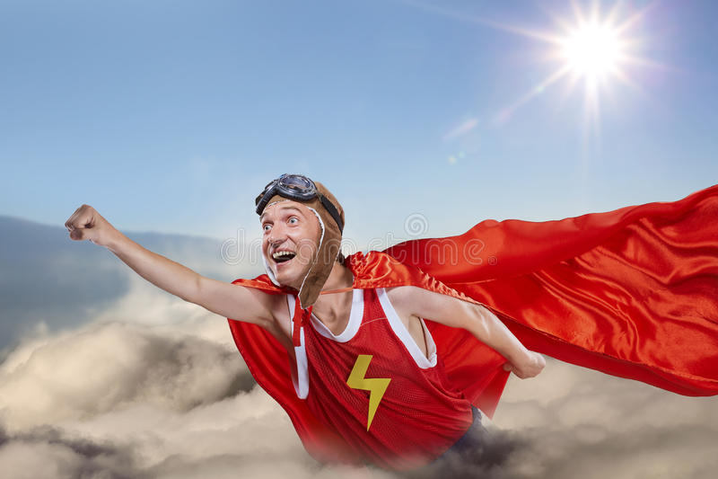 Una mosca divertida del superhéroe sobre las nubes en el cielo foto de archivo