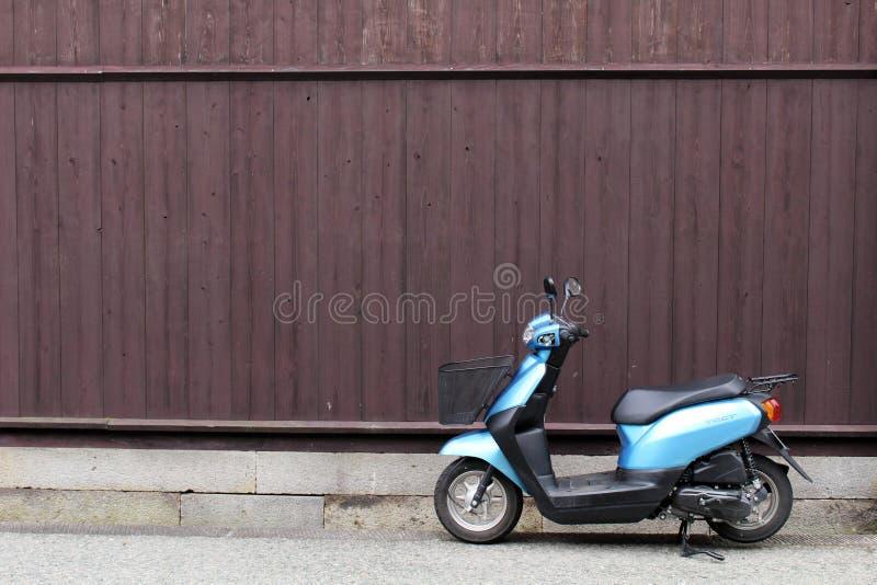 Una motocicleta parqueó delante de la pared de madera en Takayama imágenes de archivo libres de regalías