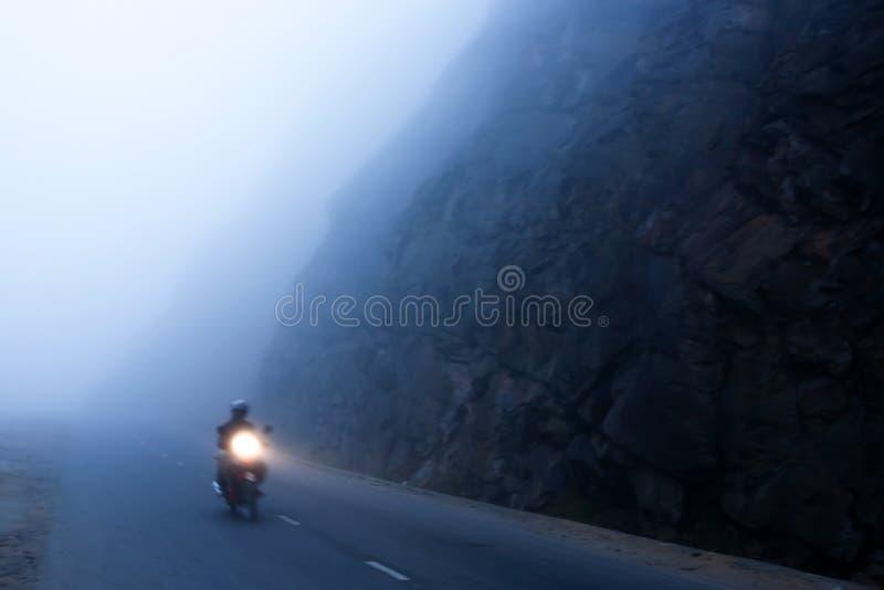 Una motocicleta que monta masculina no identificada en el camino oscuro de la montaña brumosa, carretera de asfalto mística en la foto de archivo libre de regalías