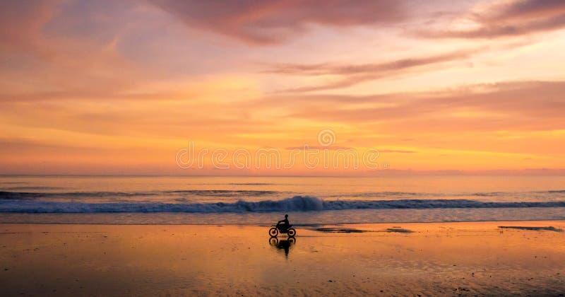 Una motocicleta y un jinete solitarios que conducen a lo largo de una playa en la puesta del sol imagenes de archivo