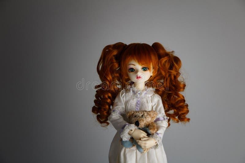 Una muñeca con el pelo rojo enorme en un vestido antiguo imagenes de archivo