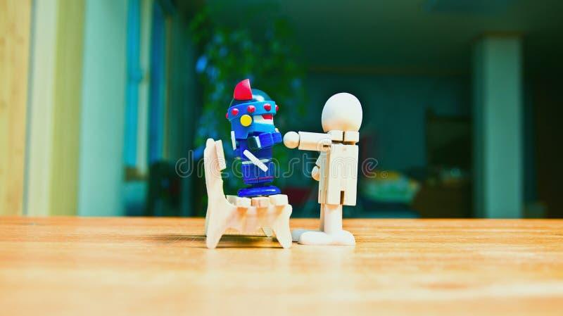 Una muñeca de madera que plantea una amenaza para un robot que se sienta en un banco fotografía de archivo libre de regalías