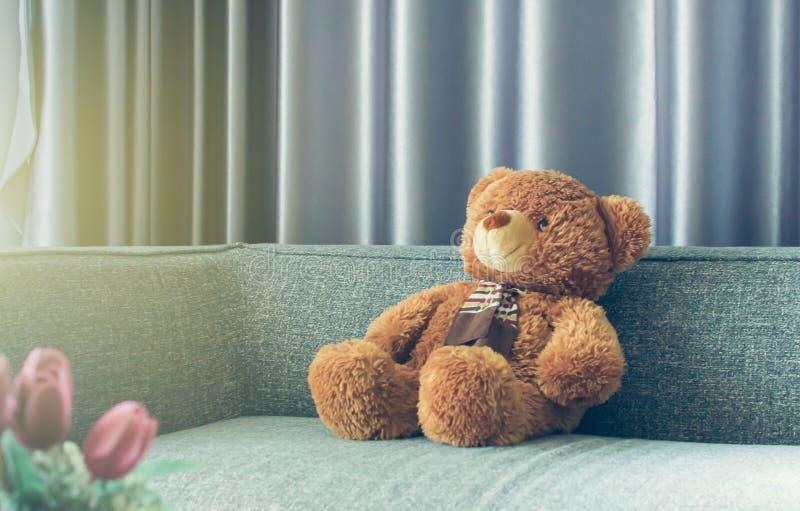 Una muñeca en el sofá en sala de estar imagen de archivo