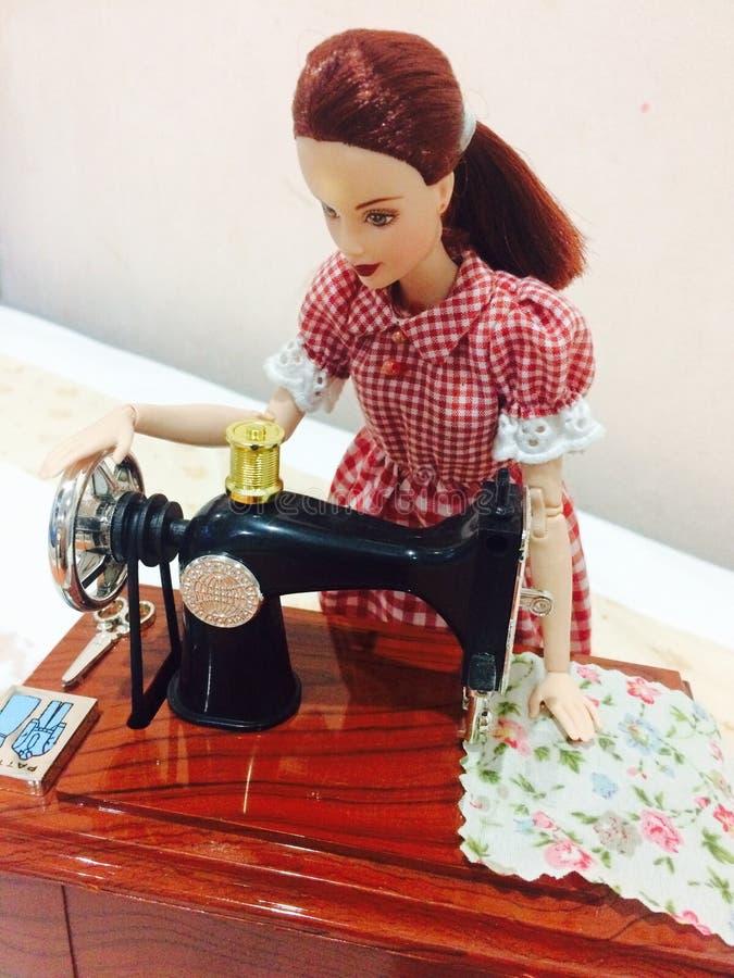 Una muñeca hermosa de barbie está cosiendo su ropa imagen de archivo libre de regalías