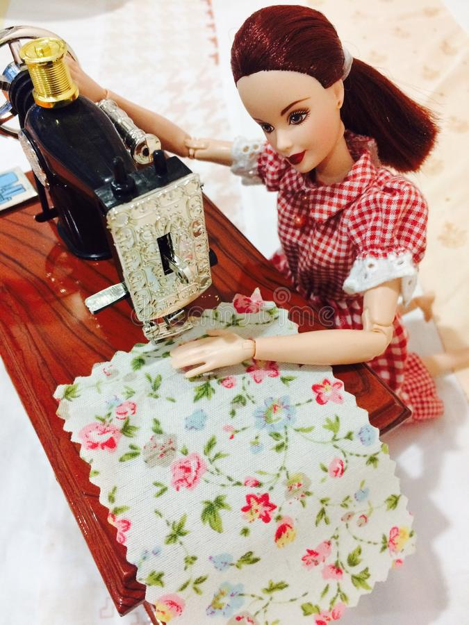 Una muñeca hermosa de barbie está cosiendo su ropa fotografía de archivo libre de regalías