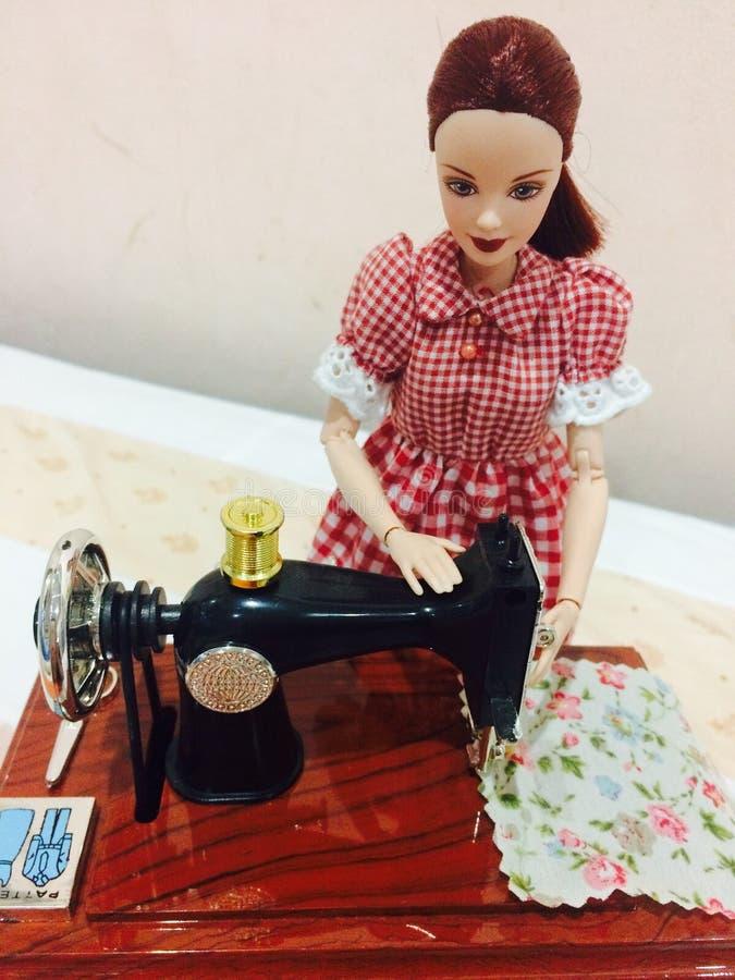 Una muñeca hermosa de barbie está cosiendo su ropa fotos de archivo libres de regalías