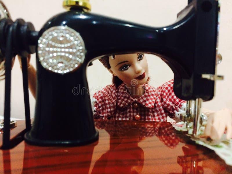 Una muñeca hermosa de barbie está cosiendo su ropa imagenes de archivo