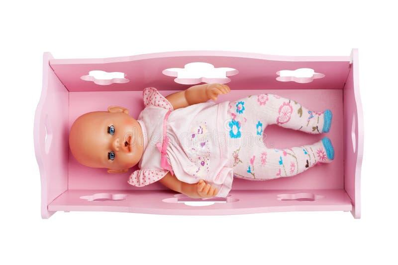 Una muñeca que pone en el pesebre rosado fotos de archivo libres de regalías