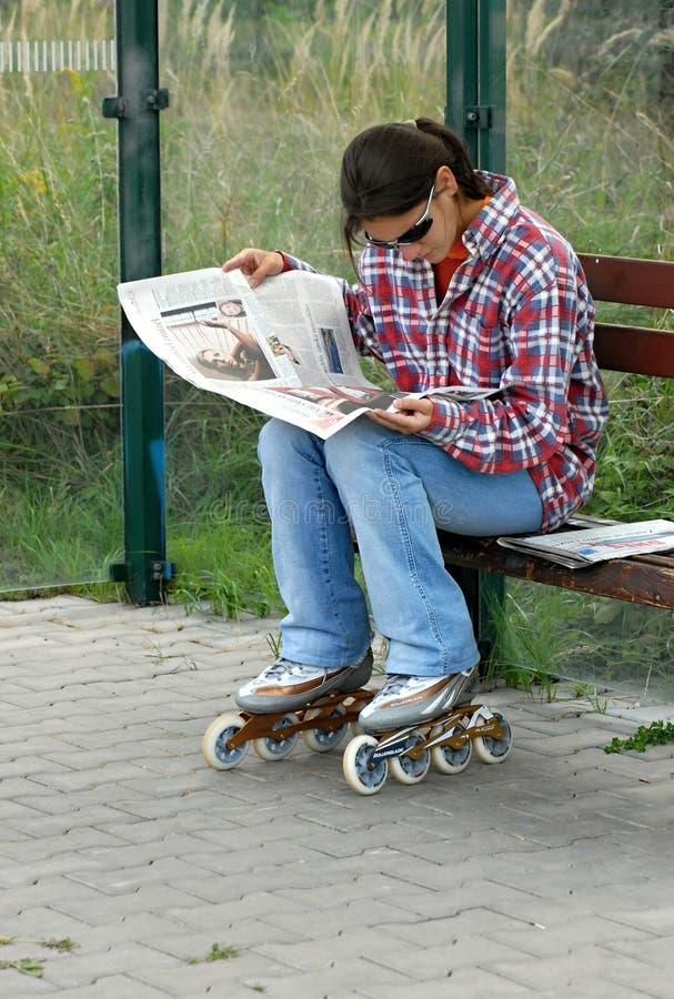 Una muchacha adentro en línea en una parada de autobús lee un periódico fotografía de archivo libre de regalías