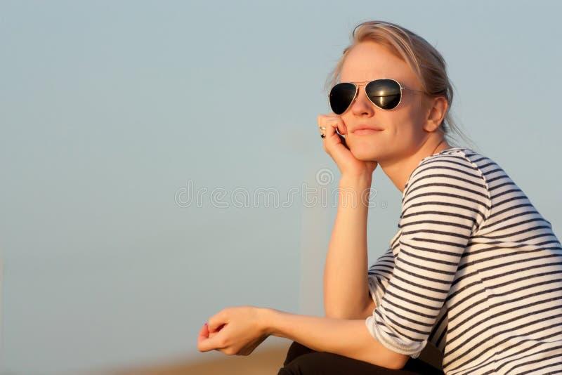 Una muchacha admira la puesta del sol fotografía de archivo