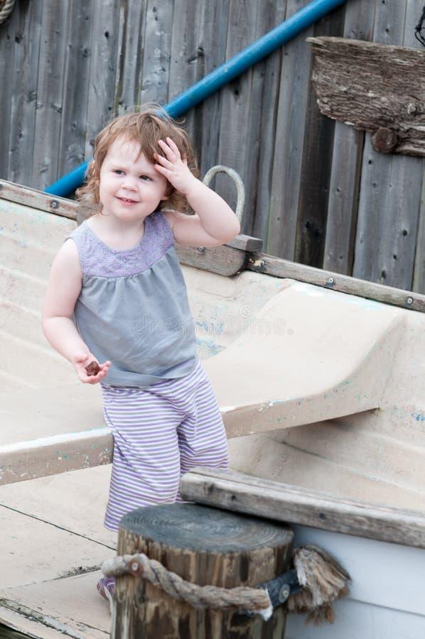 Una muchacha adorable que se sienta feliz en un pequeño barco de fila al lado de los posts del amarre fotos de archivo libres de regalías