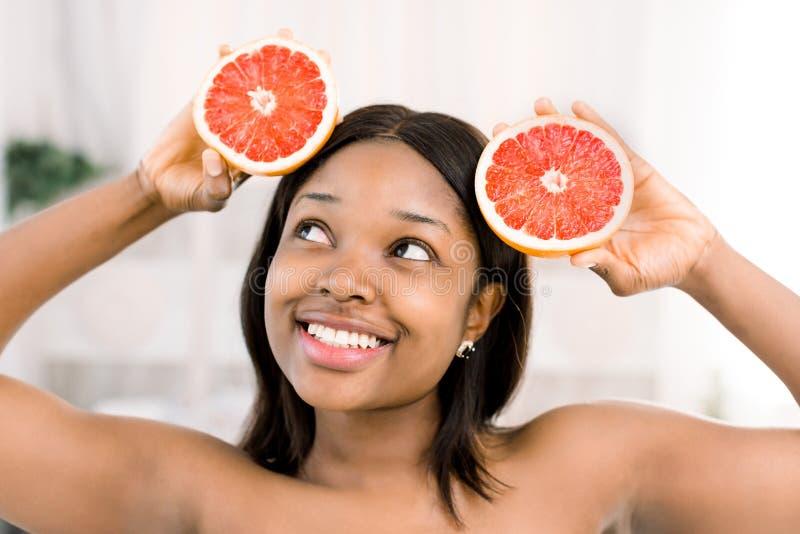 Una muchacha africana atractiva joven se sostiene en sus halfs de las manos del pomelo Concepto del cuidado de piel foto de archivo