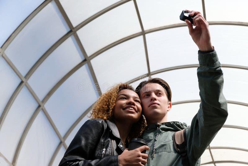 Una muchacha afroamericana hermosa moderna sonríe cuando así como un individuo blanco hacen selfi en una cámara de la acción lind fotos de archivo libres de regalías