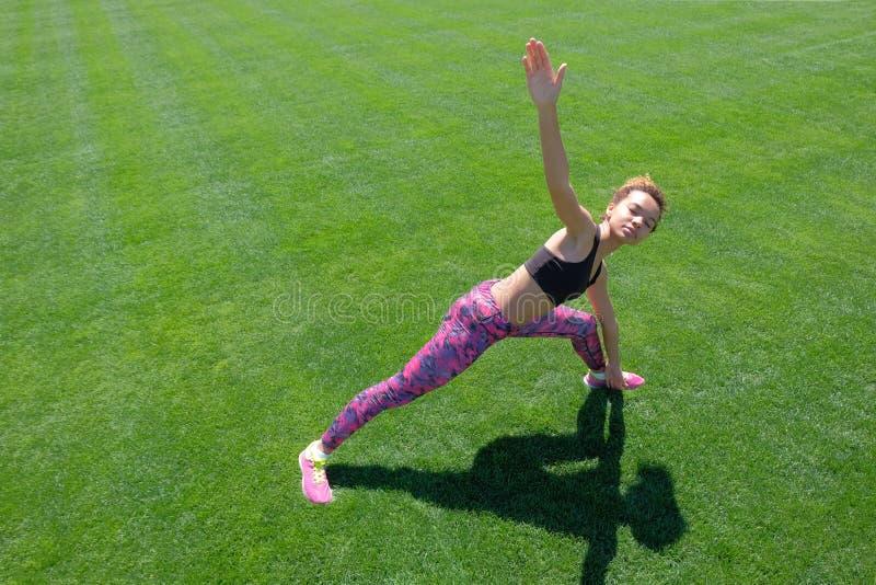 Una muchacha afroamericana joven en una camiseta negra, pantalones rosados y zapatillas de deporte haciendo deportes ejercita en  imagen de archivo libre de regalías