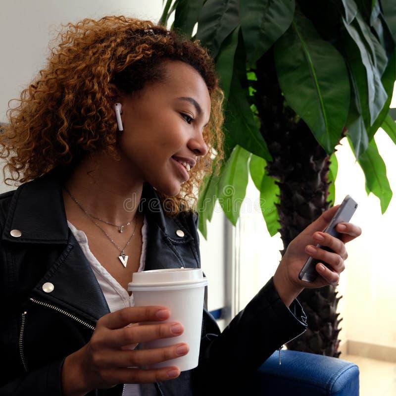 Una muchacha afroamericana joven hermosa en una chaqueta negra con los airpairs en su oído sonríe, sostiene un vidrio blanco en e imágenes de archivo libres de regalías