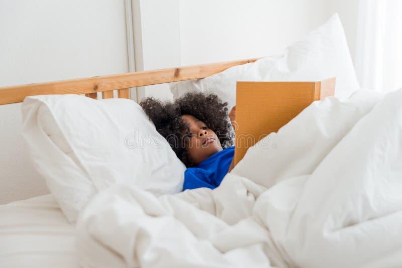 Una muchacha afroamericana linda del pequeño niño que lee un libro imagen de archivo