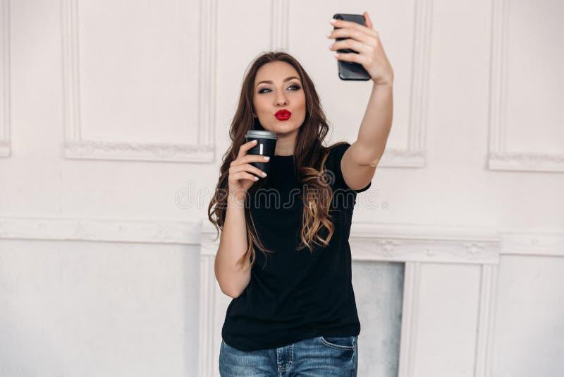 Una muchacha agradable con el pelo oscuro con los labios brillantes rojos, controles al vidrio de café en su mano, y envía besos  fotos de archivo