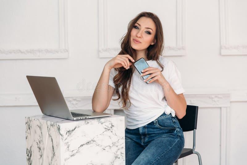 Una muchacha agradable con el pelo oscuro y los ojos grises se sienta en una tabla en un café y trabaja para su ordenador portáti foto de archivo libre de regalías