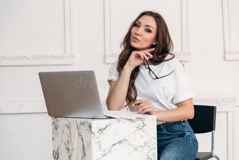 Una muchacha agradable vestida en ropa moderna se sienta en una tabla en un café ligero, sacada sus vidrios, y decidida para desc foto de archivo libre de regalías