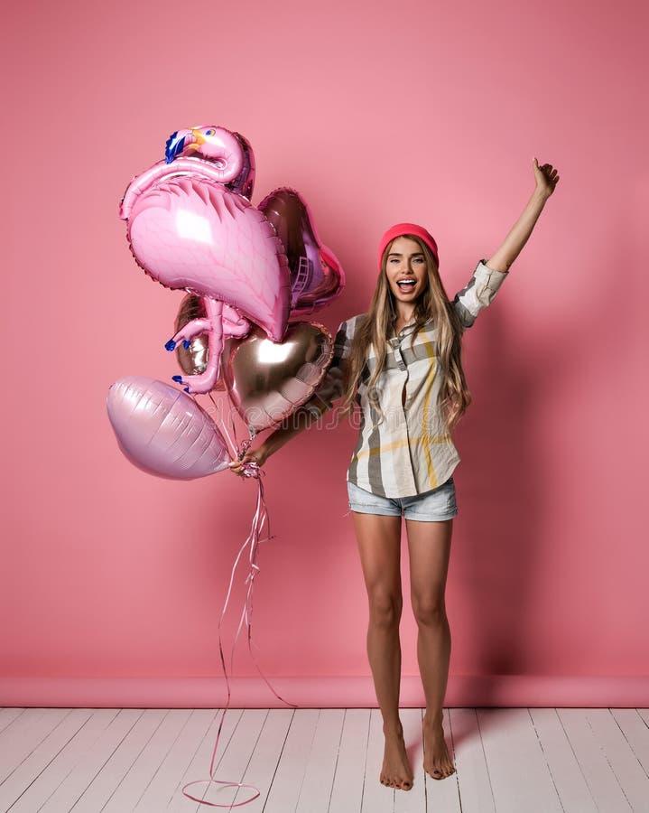 Una muchacha alegre joven hermosa está sosteniendo un manojo de globos rosados en un fondo en colores pastel rosado fotos de archivo