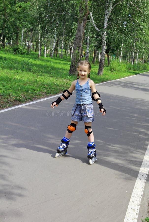 Una muchacha aprende montar un roller-skating imagen de archivo