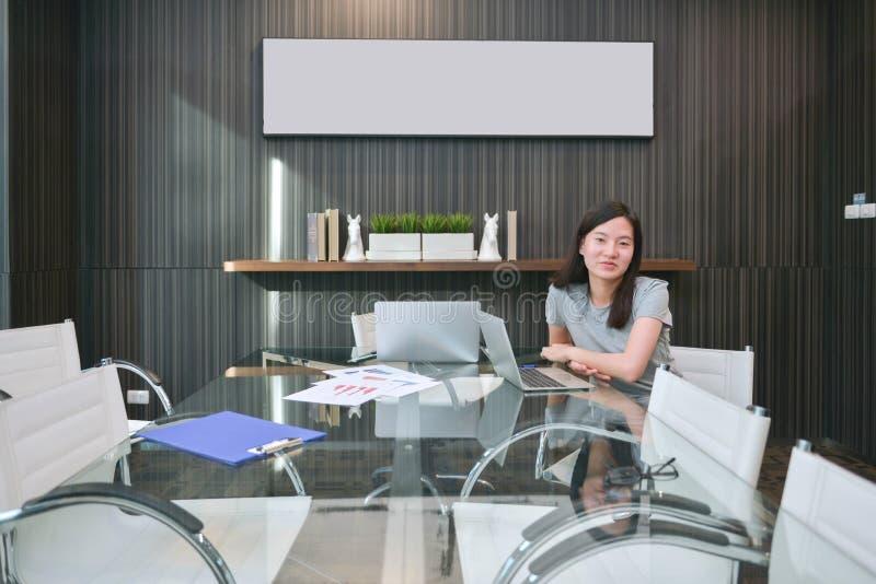 Una muchacha asiática en sala de reunión en concepto del negocio con imagen en blanco imagen de archivo